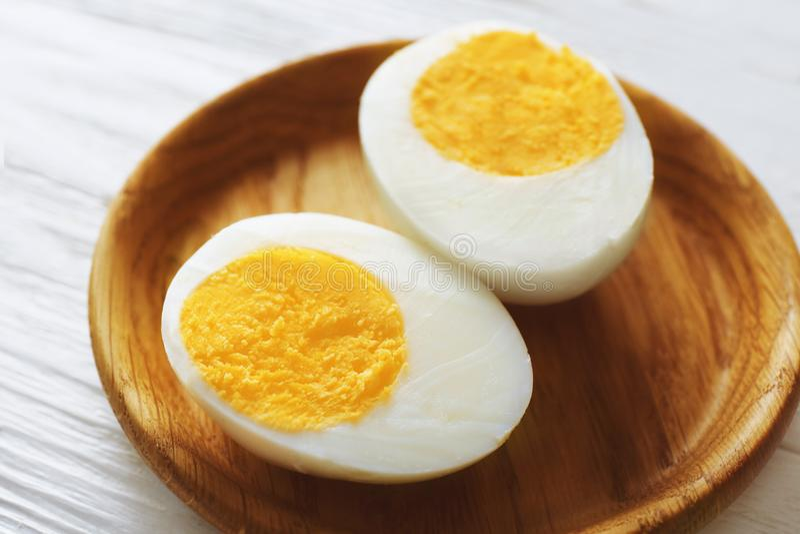 Bandeja de madeira com o ovo cozido duro cortado na tabela branca fotografia de stock royalty free
