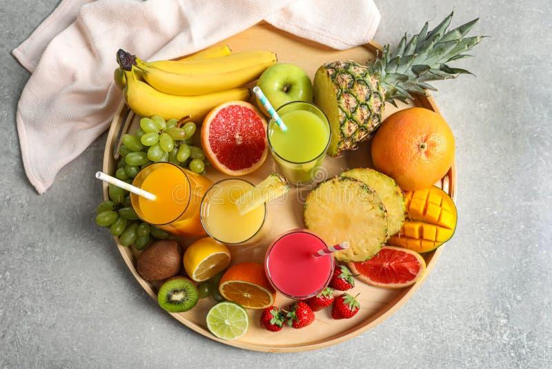 Bandeja de madeira com vidros de sucos diferentes e de frutos frescos na tabela fotos de stock