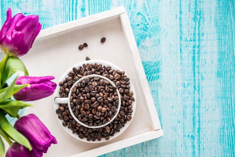 Bandeja de madera del vintage con la taza de la porcelana por completo de granos de café y de flores rosadas en el fondo elegante fotografía de archivo libre de regalías