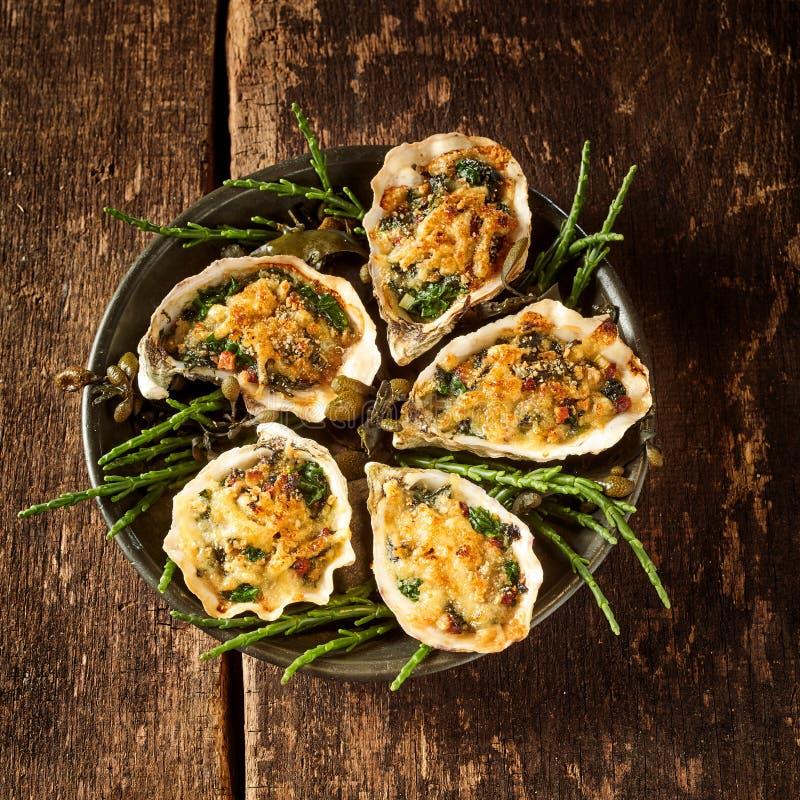 Bandeja de ostras com cobertura do Gratin na tabela fotografia de stock royalty free