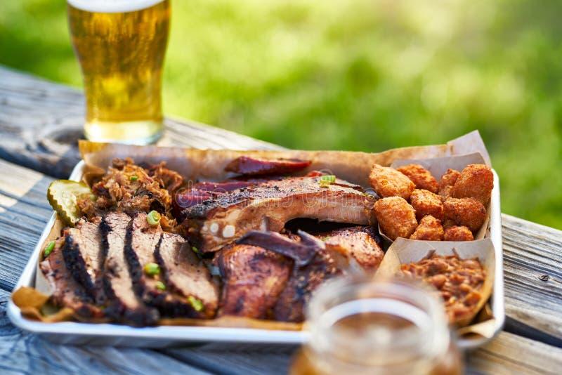 Bandeja de parte externa fumado do estilo do BBQ de texas das carnes na tabela de piquenique no dia de verão ensolarado fotografia de stock