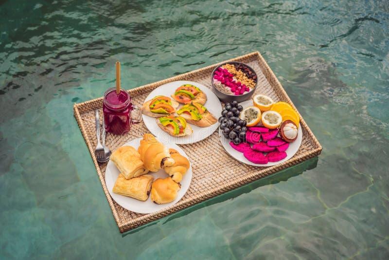 Bandeja del desayuno en piscina, desayuno flotante en smoothies del hotel de lujo y placa de la fruta, cuenco del smoothie por foto de archivo