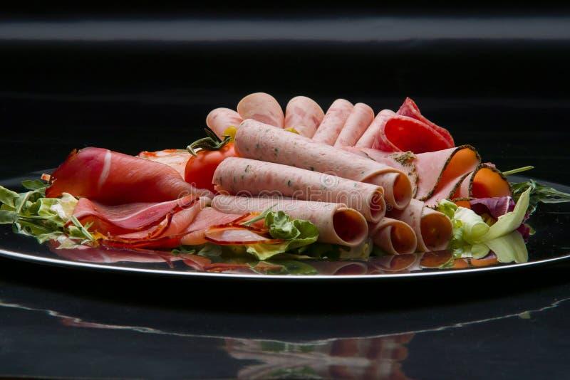 Bandeja do alimento com salame delicioso, partes de presunto cortado, salsicha, tomates, salada e vegetal - imagem de stock royalty free