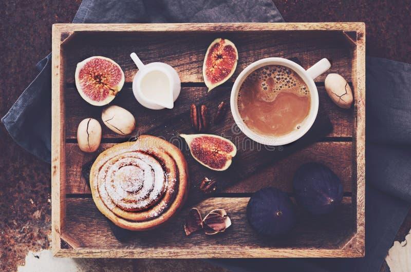Bandeja do café da manhã - xícara de café com creme, rolo de canela, os figos frescos e as nozes-pecã fotos de stock