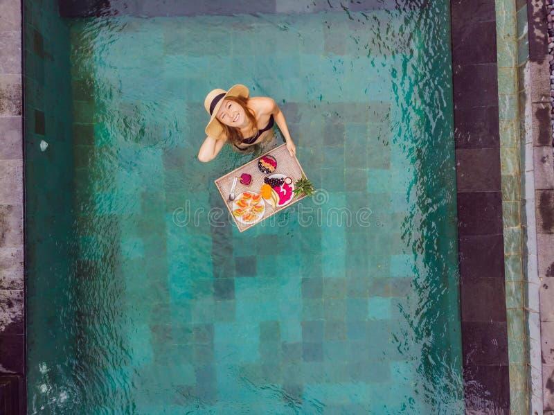 Bandeja do caf? da manh? na piscina, caf? da manh? de flutua??o no hotel de luxo Menina que relaxa nos batidos bebendo da associa fotos de stock