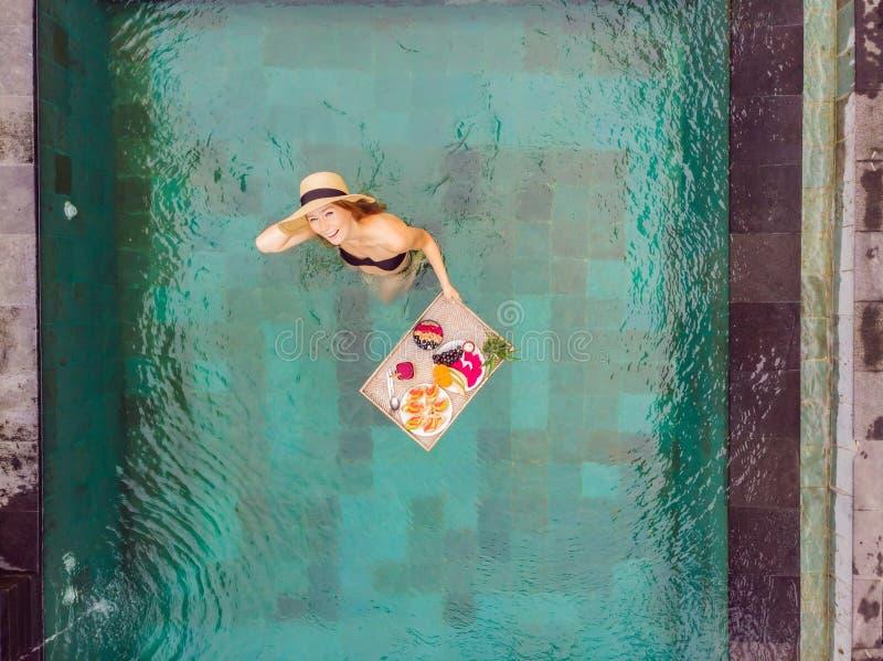 Bandeja do caf? da manh? na piscina, caf? da manh? de flutua??o no hotel de luxo Menina que relaxa nos batidos bebendo da associa imagens de stock