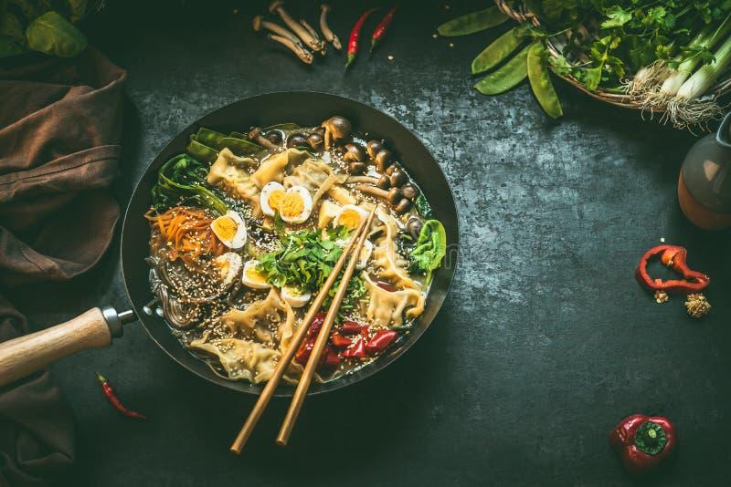 Bandeja do frigideira chinesa com o potenciômetro e os hashis quentes coreanos do vegetariano no fundo rústico escuro da mesa de  fotografia de stock royalty free