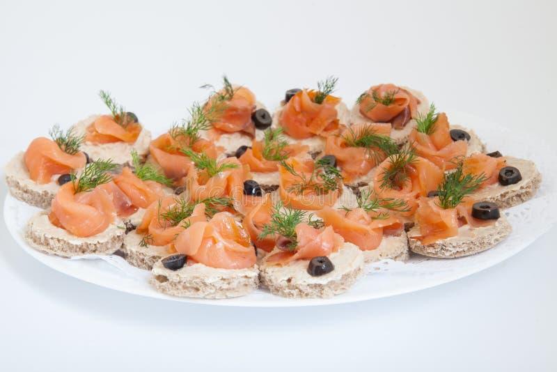 Bandeja do partido de aperitivos do salmão fumado do tamanho da mordida imagem de stock