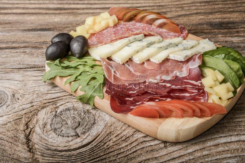 Bandeja do queijo azul e das carnes frias com salame, prosciutto do presunto das fatias, queijo, azeitonas e ervas imagem de stock