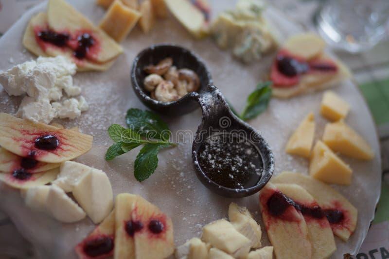 Bandeja do queijo com fatia de fruto, de mel e de porca no centro na placa de madeira Placa do jantar, petisco foto de stock