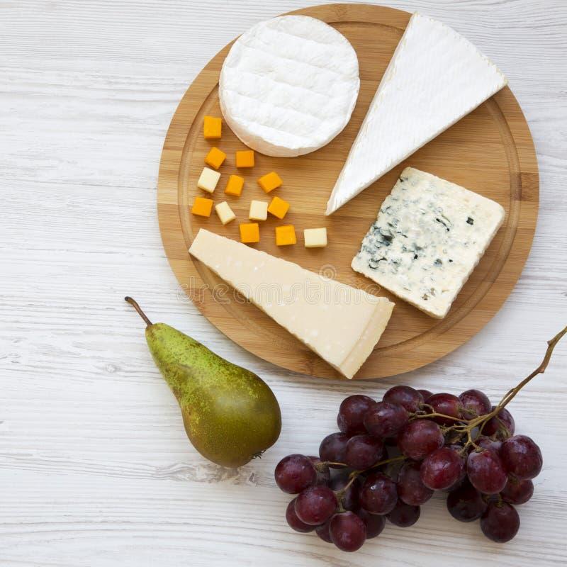 Bandeja do queijo com frutos em um fundo de madeira branco Alimento para o vinho, vista superior Configuração lisa, de cima de Cl imagens de stock royalty free