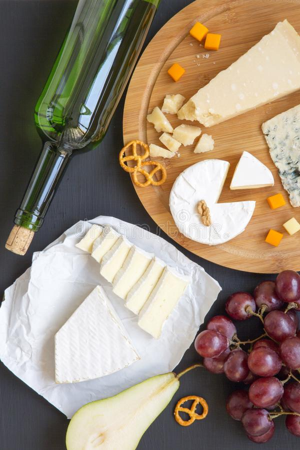 Bandeja do queijo com vinho, frutos, pretzeis e nozes no fundo escuro, vista superior foto de stock