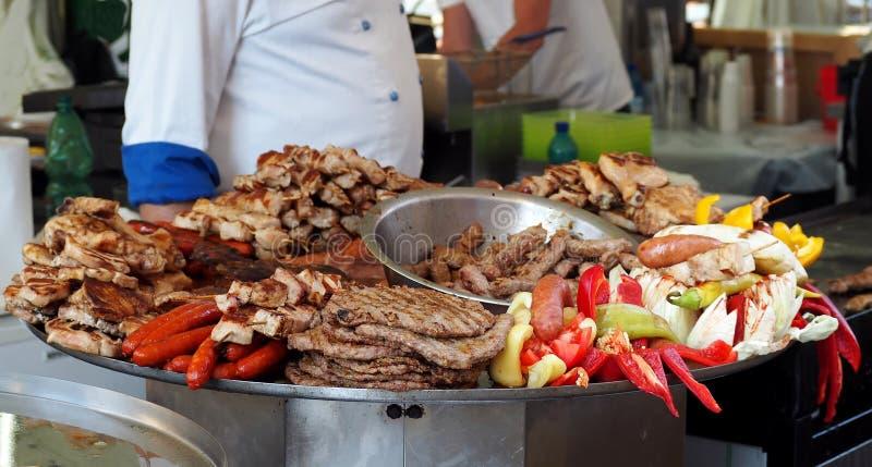 Bandeja heated grande con la comida serbia tradicional de la calle Las carnes asadas a la parrilla típicas con las verduras imagenes de archivo