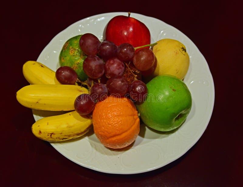 Bandeja inteira do fruto na placa branca na tabela de madeira foto de stock