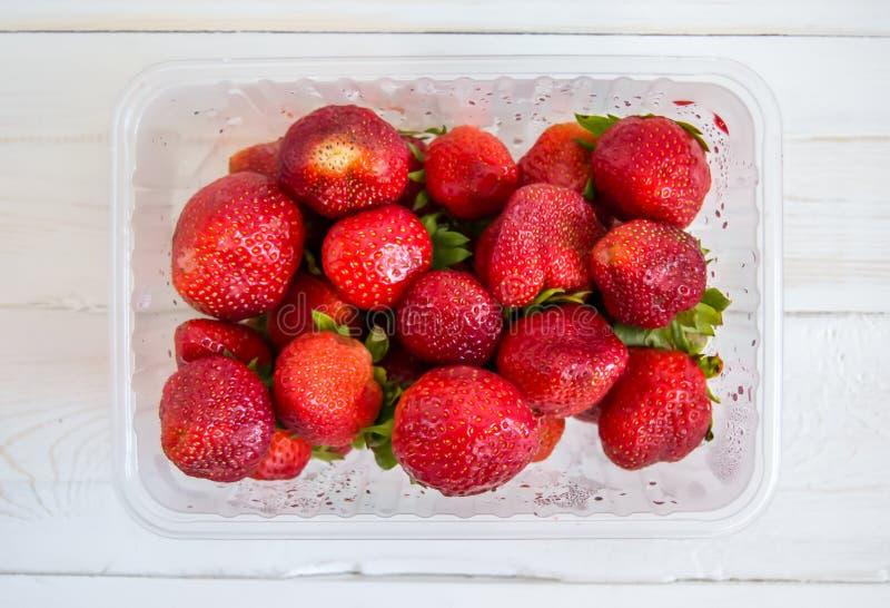 Bandeja plástica con las fresas rojas en una opinión de top de madera blanca del fondo fotografía de archivo libre de regalías