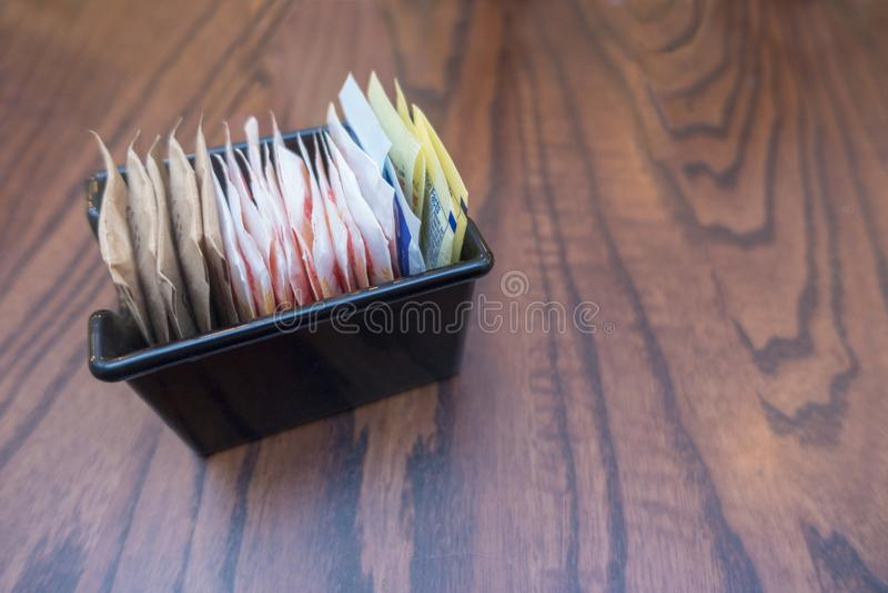 Bandeja preta pequena com os edulcorantes do saco do açúcar foto de stock