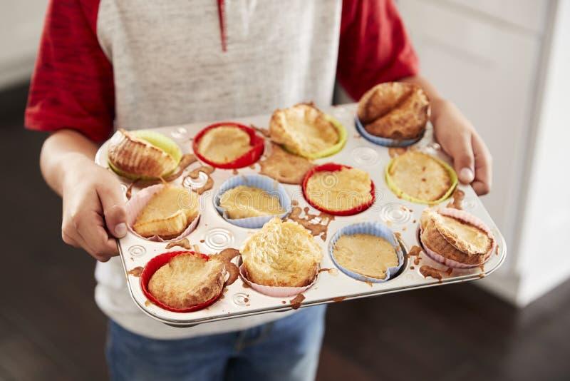 Bandeja que cocía de la tenencia del muchacho, presentando a las tortas lo ha cocido a la cámara, mediados de sección, cierre par fotos de archivo