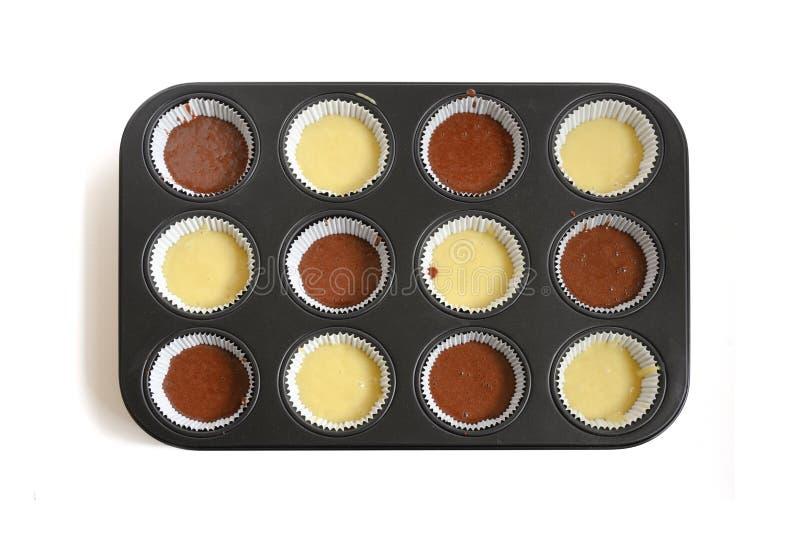 Bandeja que cuece del mollete llenada de dos clases de pasta para las magdalenas deliciosas, opinión de la torta de alto ángulo d fotografía de archivo