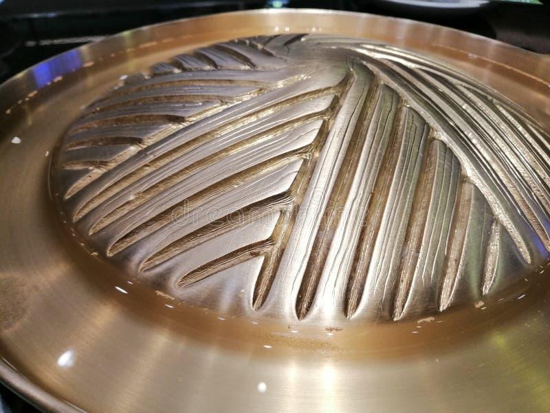 Bandejas de bronze para grelhar e assado, ?gua em uma bandeja de bronze, jantar no restaurante fotos de stock