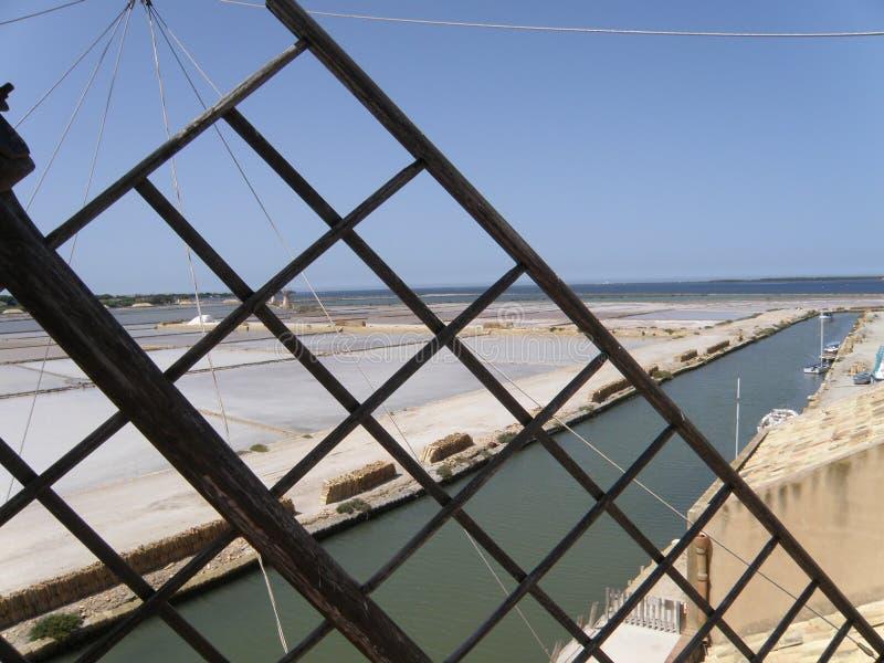 Bandejas de sal do Salina em Sicília, como visto completamente as lâminas de um moinho de vento imagens de stock royalty free