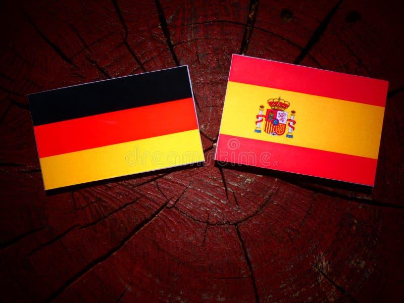 Bandera alemana con la bandera española en un tocón de árbol fotos de archivo libres de regalías