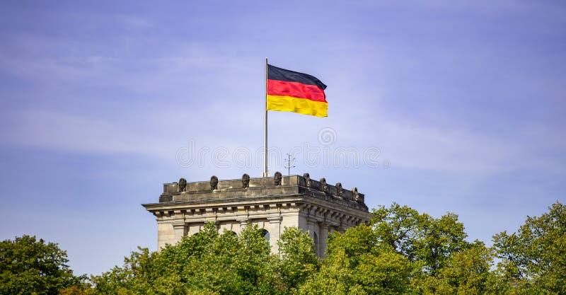 Bandera alemana que agita en la asta de bandera de plata, edificio de Reichstag en Berlín Cielo azul con el fondo de las nubes imágenes de archivo libres de regalías