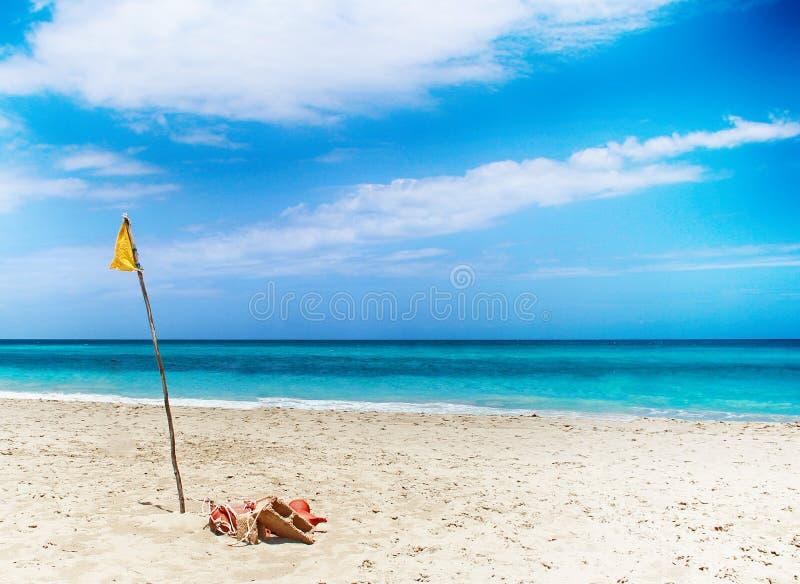 Bandera amarilla en arena en la playa por el mar Cerca es Océano Atlántico Se sitúa en Cuba, del Caribe imagen de archivo