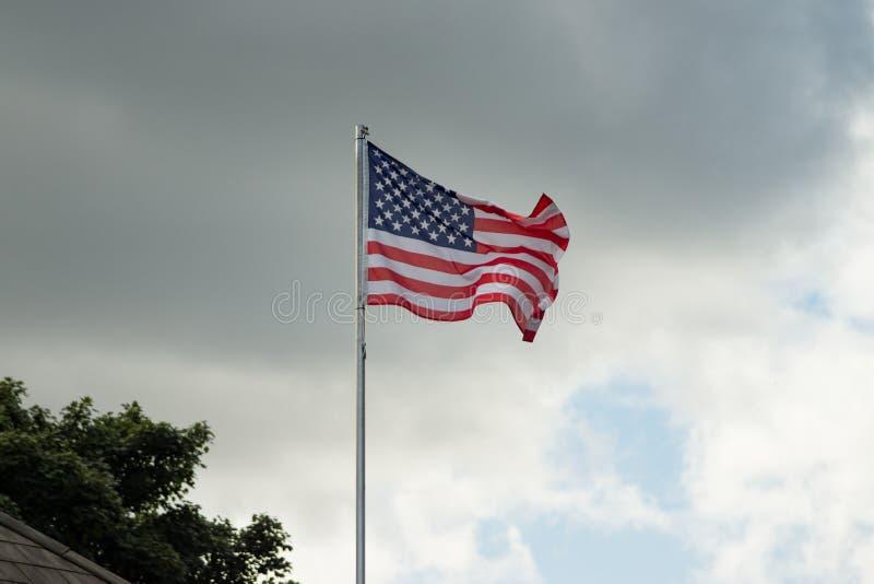 Bandera americana, barras y estrellas, volando de una asta de bandera contra las nubes oscuras, tempestuosas en el fondo imágenes de archivo libres de regalías