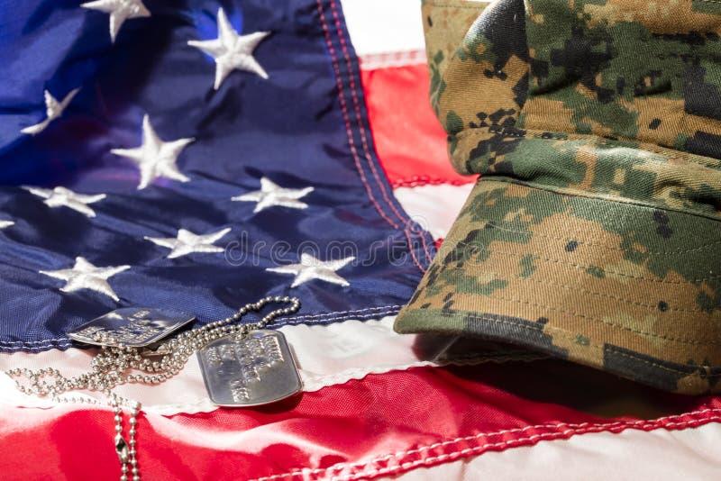 Bandera americana con la cubierta y las placas de identificación de los militares imagenes de archivo