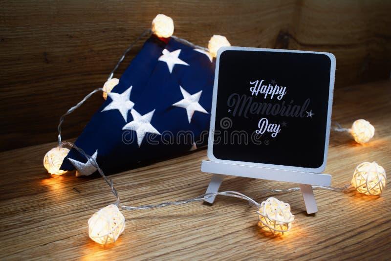 Bandera americana con la guirnalda del tablero de tiza en un fondo de madera para el Día de los caídos y otros días de fiesta  fotos de archivo