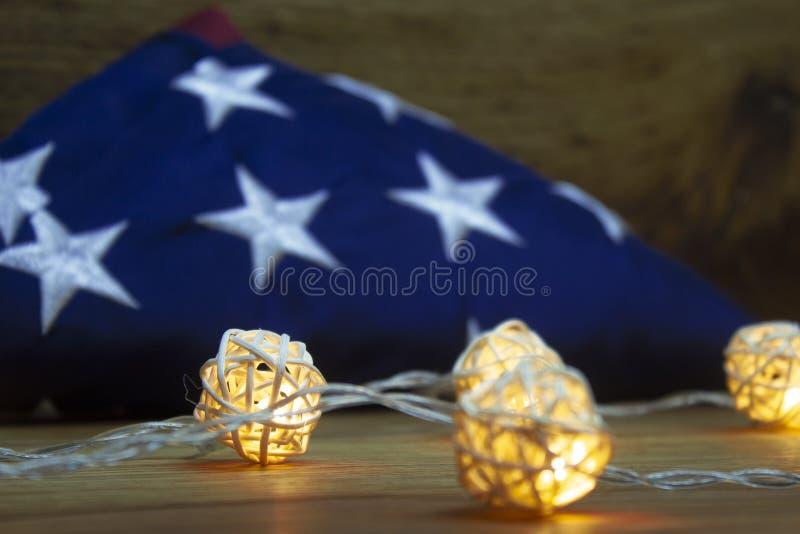 Bandera americana con la guirnalda en un fondo de madera para el D?a de los ca?dos y otros d?as de fiesta de los Estados Unidos d foto de archivo