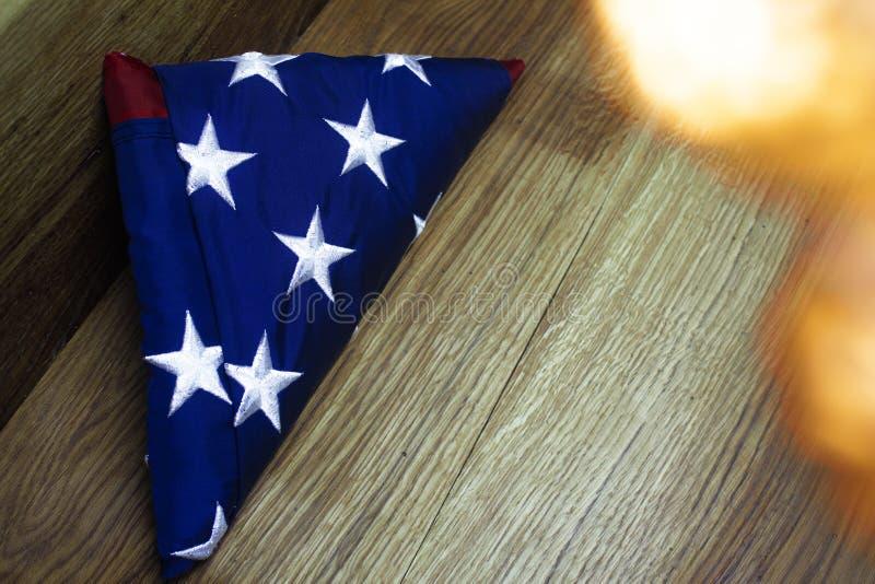 Bandera americana con la guirnalda en un fondo de madera para el D?a de los ca?dos y otros d?as de fiesta de los Estados Unidos d fotos de archivo