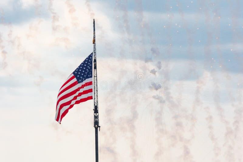 Bandera americana con los fuegos artificiales del vuelo imagenes de archivo