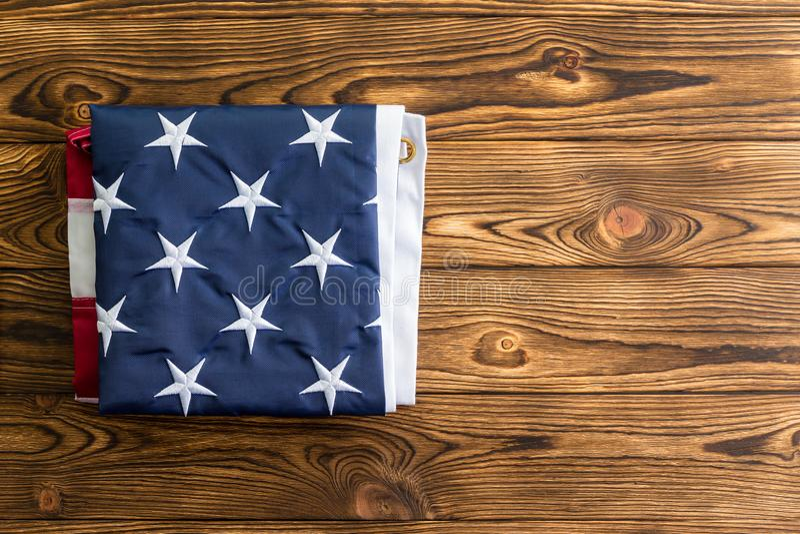 Bandera americana cuidadosamente doblada en una tabla de madera imagenes de archivo