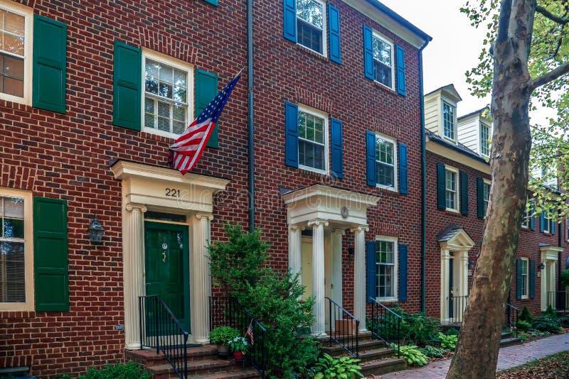 Bandera americana delante de casas americanas típicas Maryland, los E fotografía de archivo libre de regalías