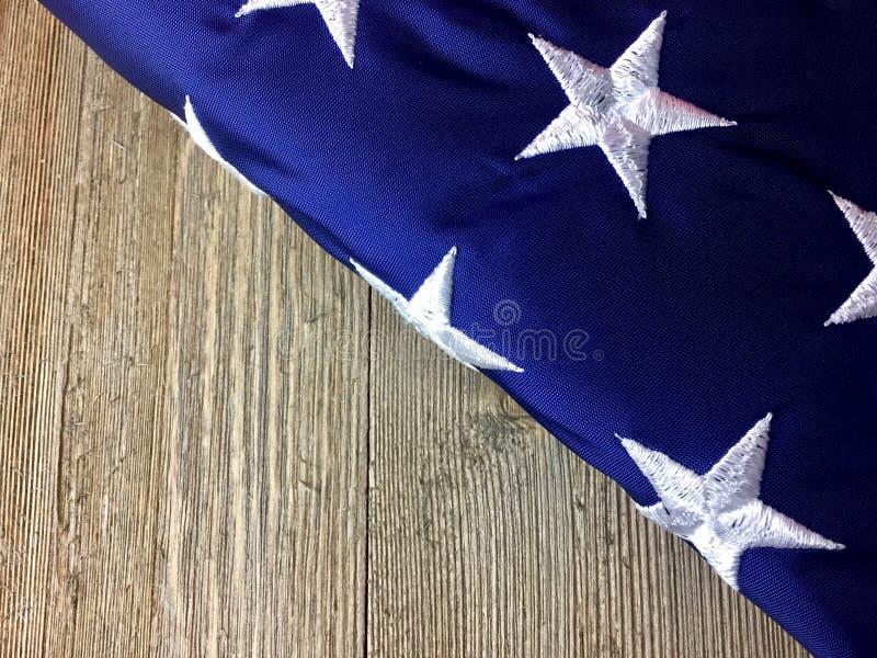 Bandera americana doblada en la superficie de madera imagen de archivo libre de regalías