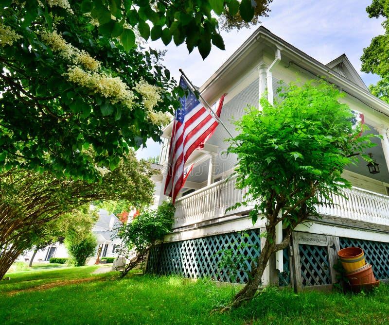 Bandera americana exhibida orgulloso del pórche de entrada blanco del viejo hogar del estilo de Nueva Inglaterra foto de archivo libre de regalías