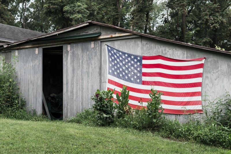 Bandera americana vieja en un granero foto de archivo