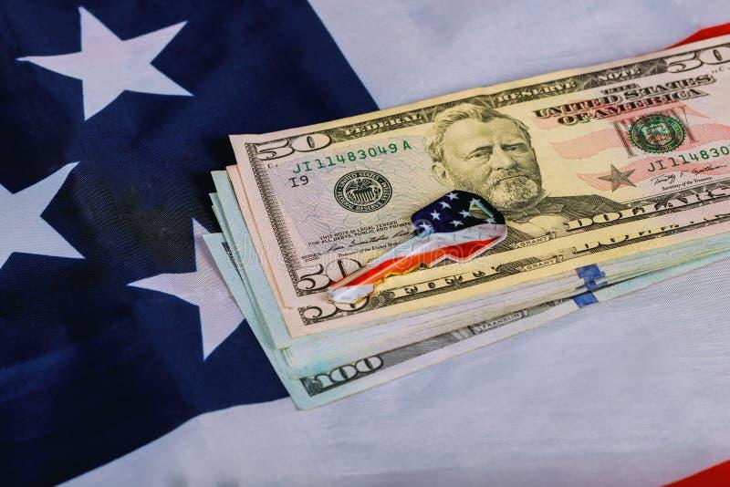 Bandera americana y dólares de EE. UU. y una llave de la casa en el plan arquitectónico del apartamento Propiedades inmobiliarias imagenes de archivo