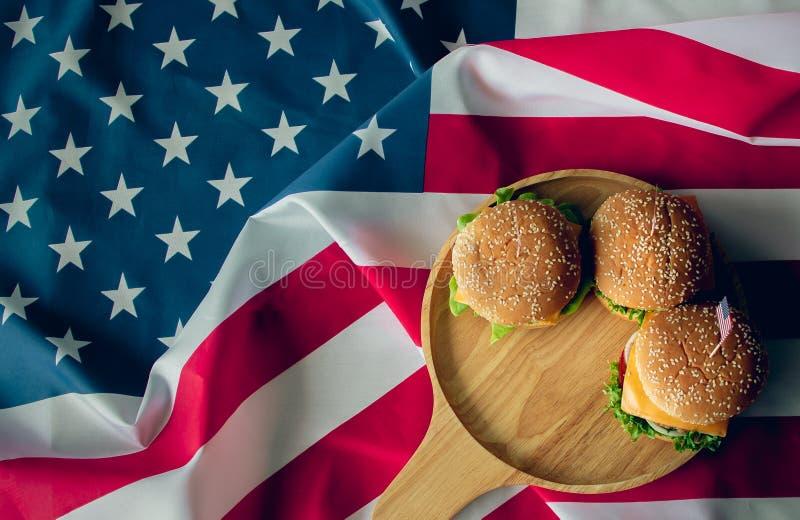 Bandera americana y hamburguesa que es el s?mbolo del pa?s foto de archivo