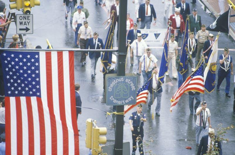 Bandera americana y veteranos que marchan en desfile, los Estados Unidos de América fotografía de archivo