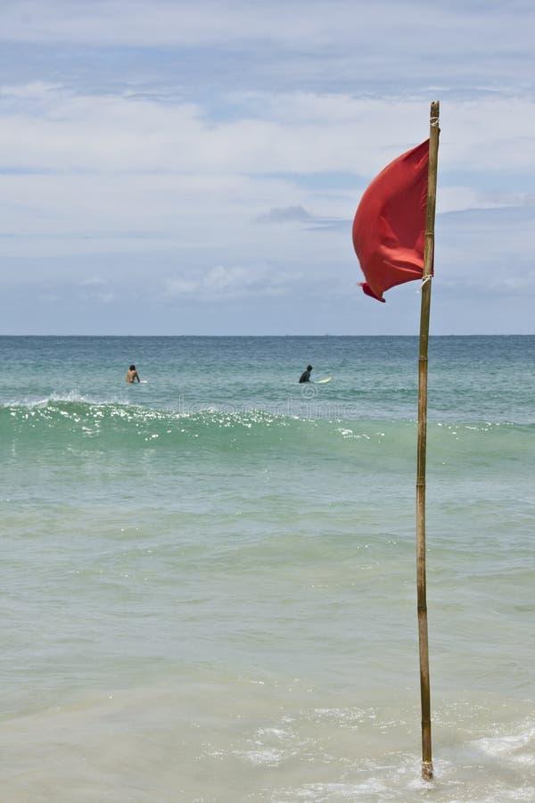 Bandera amonestadora roja en el agua de la playa imagen de archivo