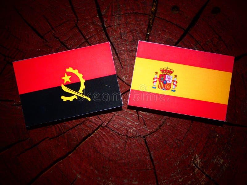 Bandera angolana con la bandera española en un tocón de árbol imágenes de archivo libres de regalías