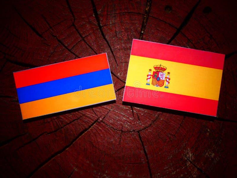 Bandera armenia con la bandera española en un tocón de árbol foto de archivo libre de regalías