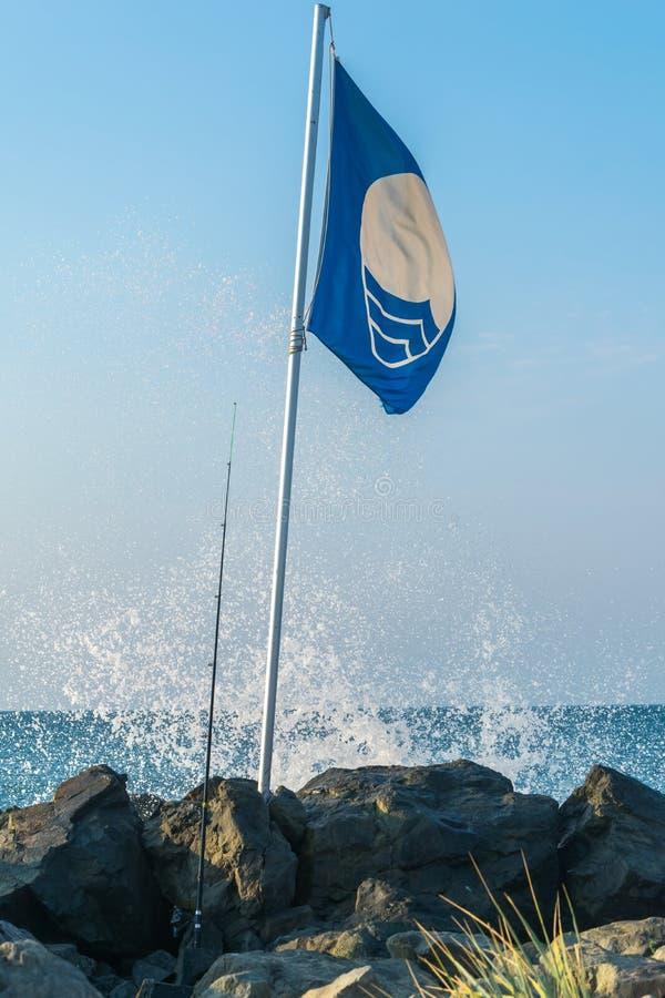 Bandera azul y caña de pescar por el mar imagen de archivo