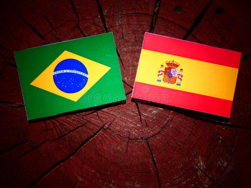 Bandera brasileña con la bandera española en un tocón de árbol fotografía de archivo libre de regalías