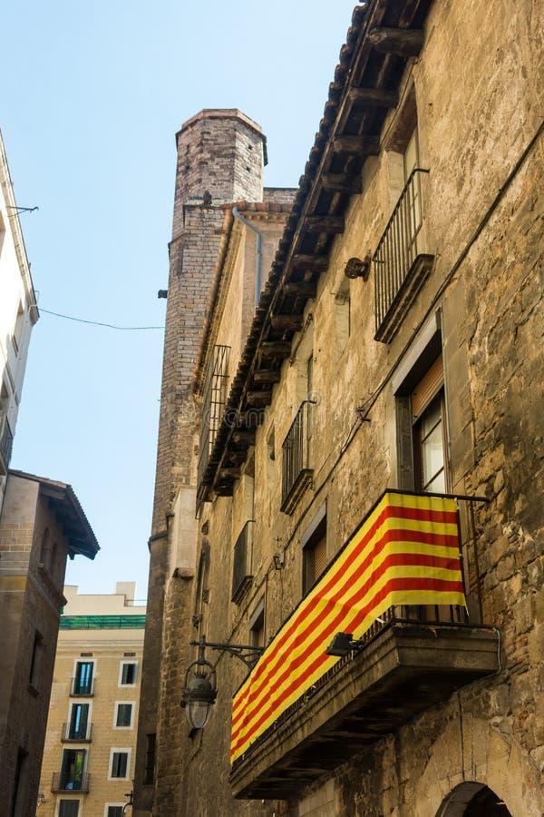 Bandera catalana, colgando en un balcón, en el cuarto gótico de la barra imagenes de archivo