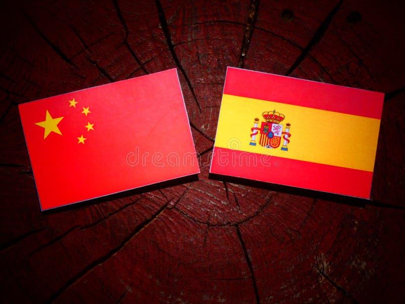 Bandera china con la bandera española en un tocón de árbol imágenes de archivo libres de regalías
