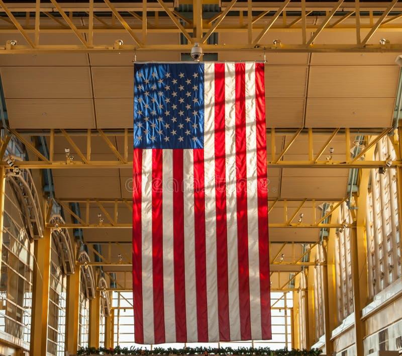 Bandera colgante gigante de los E.E.U.U. en el aeropuerto imagenes de archivo