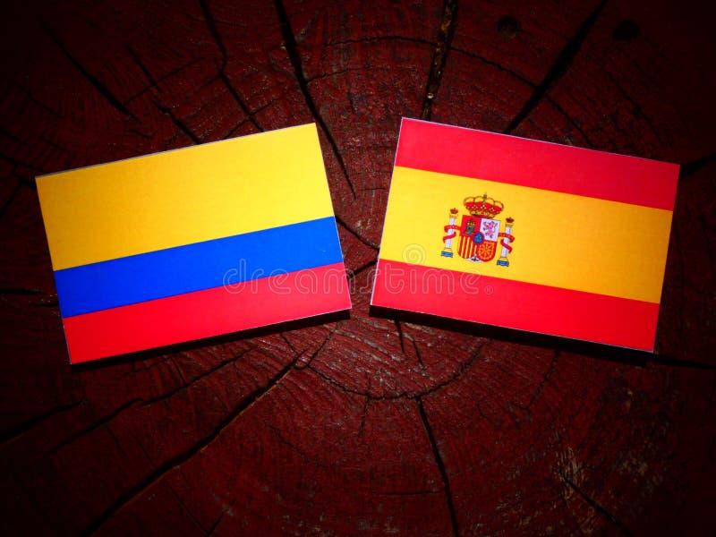 Bandera colombiana con la bandera española en un tocón de árbol imagen de archivo libre de regalías